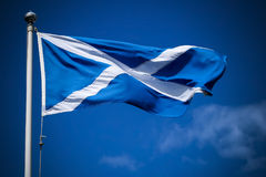 Schottland-Flaggenfliegen im Sonnenschein gegen blauen Himmel Stockfotos