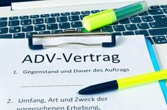 Schowek z kontraktem i inskrypcja w niemieckich ADV w i trwaniu przeciw angielskim ADV kontrakcie, przedmiocie i zdjęcie royalty free