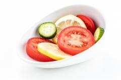 Schräg gelegene weiße Schüssel mit roten Tomaten- und Gurkenscheiben der kreisförmigen gelben Zitrone Lizenzfreie Stockbilder