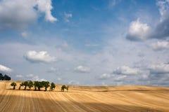 Schräges Feld mit eindrucksvollem Himmel und Wolken Lizenzfreie Stockfotografie
