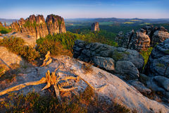 Schrammsteine, beautiful evening view over sandstone cliff into deep misty valley in Saxony Switzerland, evening background, the f. Og is orange due to sunset Stock Photos