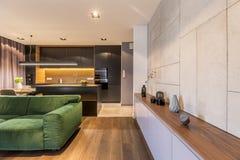 Schrank mit Vasen und Uhr im modernen eleganten Wohnzimmerinnenraum mit grünem Samtsofa und dunkler Küchenecke stockfotografie