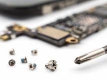 Schraube und Schraubenzieher mit unscharfen Smartphonekomponenten lizenzfreies stockfoto