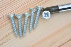 Schrauben mit Schraubenzieher mit Holz Stockfotos