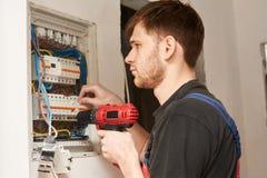 Schraubende Ausrüstung des Elektrikererbauer-Ingenieurs im Sicherungskasten Stockbild
