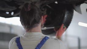 Schraubende Details des Berufsingenieurs des Autos mit Spezialwerkzeug auf angehobenem Automobil am Reparaturtankstelleabschluß o stock video footage