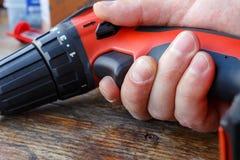 Schraubenzieher in der Hand gegen die Holztischnahaufnahme Stockfotografie