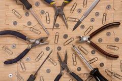 Schraubenzieher, Messer, Drahtzangen, Zangen, Knöpfe und Büroklammern auf einer Holzoberfläche Werkstattmodellbauten Lizenzfreies Stockbild