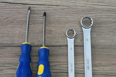 Schraubenzieher und Schlüssel lokalisiert auf Holztisch Tun Sie es Yourse lizenzfreie stockfotos