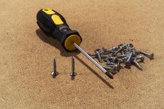 Schraubenzieher und Schrauben am hölzernen Hintergrund Stockfotos