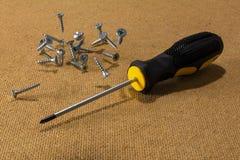 Schraubenzieher und zerstreute Schrauben am hölzernen Hintergrund Lizenzfreie Stockfotos