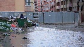 Schreckliche Ansicht der Müllkippe im Wohnyard und in der enormen schmutzigen Pfütze, durch die Person versucht, zu überschreiten stock video