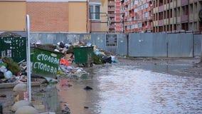 Schreckliche Ansichtdump-Abfalltaschen mit dem Abfall, der nahe bei Abfalleimern und enormer Pfütze auf defekter Straße im Wohnya stock video