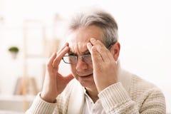 Schreckliche Migräne Trauriger älterer Mann, der Tempel berührt stockbild