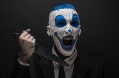 Schrecklicher Clown und Halloween-Thema: Verrückter blauer Clown in einem schwarzen Anzug mit einem Messer in seiner Hand lokalis Lizenzfreies Stockbild