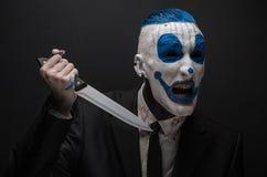 Schrecklicher Clown und Halloween-Thema: Verrückter blauer Clown in einem schwarzen Anzug mit einem Messer in seiner Hand lokalis Stockbild