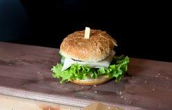 Schrecklicher Hamburger mit Kopfsalat und Käse auf einem Holzregal Lizenzfreie Stockbilder