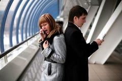 Schreeuw - mens en meisje met cellulaire telefoons Stock Afbeeldingen