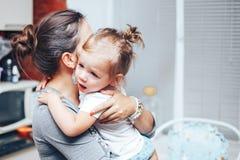 Schreeuwend meisje op moederhanden thuis stock fotografie