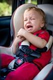 Schreeuwende babyjongen in autozetel Stock Fotografie