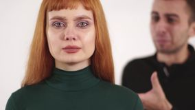 Schreeuwt de jongelui verstoorde vrouw met rood lang haar en de jonge boze mens schreeuwt terug achter haar stock videobeelden