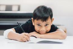 Schreiben asiatische Jungen an den verletzten Händen Notizbuch Stockbilder