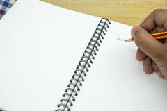 Schreiben auf ein Notizbuch Stockbild
