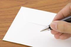 Schreiben auf einen Umschlag stockbilder