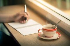 Schreiben auf Notizbuch mit Kaffeetasse Stockbild