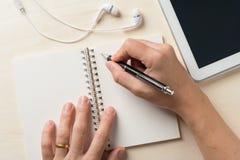 Schreiben auf Notizbuch mit kleiner Tablette Lizenzfreie Stockfotografie
