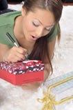 Schreiben der jungen Frau auf einer Geschenkkarte auf einem Teppich Stockfotos