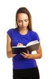 Schreiben der jungen Frau in ihrem Organisator Lizenzfreie Stockfotos