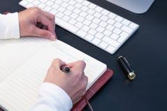 Schreiben der jungen Frau im Notizbuch auf Tischrechner und der Tastatur gesetzt auf Arbeitsschreibtisch getrennte alte Bücher Lizenzfreie Stockbilder