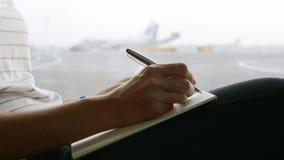 Schreiben der jungen Frau im Tagebuch am Flughafen, Nahaufnahme stock video footage
