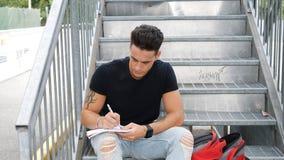 Schreiben des jungen Mannes auf Papierblatt mit Stift Stockbilder