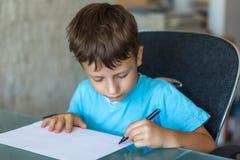 Schreiben des kleinen Jungen auf Papier stockfotografie