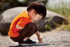 Schreiben des kleinen Jungen aus den Grund Stockfotografie