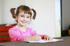 Schreiben des kleinen Mädchens auf einem Notizbuch stockfotos