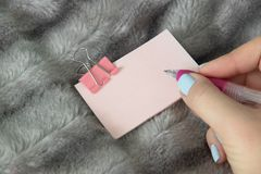 Schreiben des rosa Stiftes auf hellrosa Aufkleber mit rosa Metallklammernbriefpapier lizenzfreie stockfotos