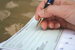 Schreiben eines Schecks Stockfotos