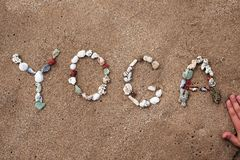 Schreiben mit Oberteiltext Yoga auf Strand Stockfotografie