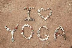 Schreiben mit Oberteiltext Yoga auf Strand Stockfotos