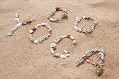 Schreiben mit Oberteiltext Yoga auf Strand Stockbilder