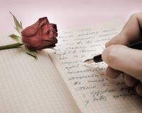 Schreiben Sie einen Liebesbrief mit einer Rose Stockfoto