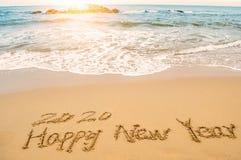 Schreiben Sie 2020 guten Rutsch ins Neue Jahr auf Strand Lizenzfreie Stockbilder