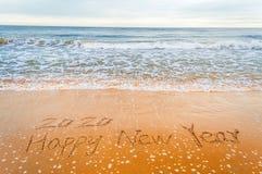 Schreiben Sie 2020 guten Rutsch ins Neue Jahr auf Strand Lizenzfreies Stockbild
