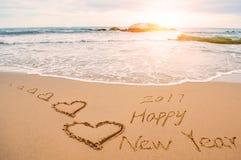 Schreiben Sie 2017 guten Rutsch ins Neue Jahr auf Strand mit Herzen Lizenzfreie Stockfotos