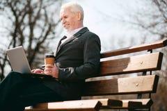 Schreibenbericht des netten älteren Geschäftsmannes stockfotografie