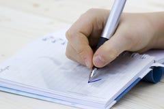 Schreibende Feder in der Hand stockbild