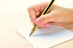 Schreibender Bleistift in der Hand Lizenzfreies Stockbild